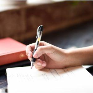 Estudiante tomando apuntes en un cuaderno