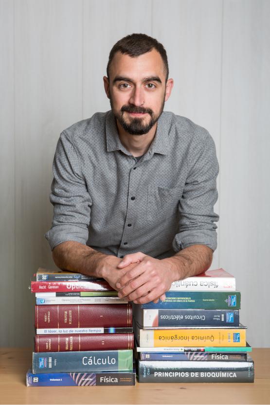 Profesor de la academia apoyado sobre una pila de libros de Física y de Química.