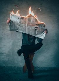 Persona leyendo un periódico en llamas.