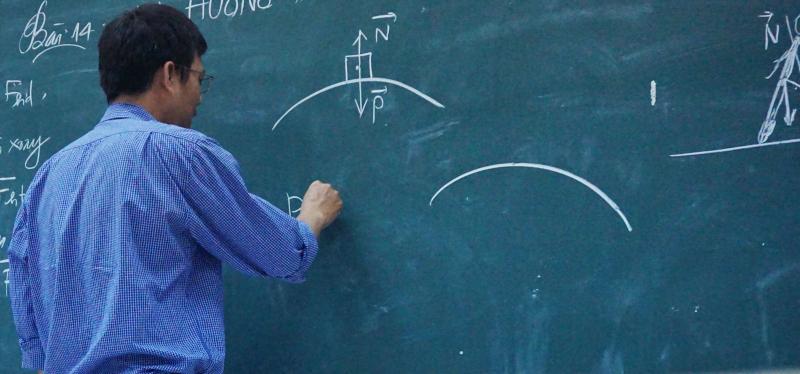 Profesor explicando un ejercicio de física en la pizarra.