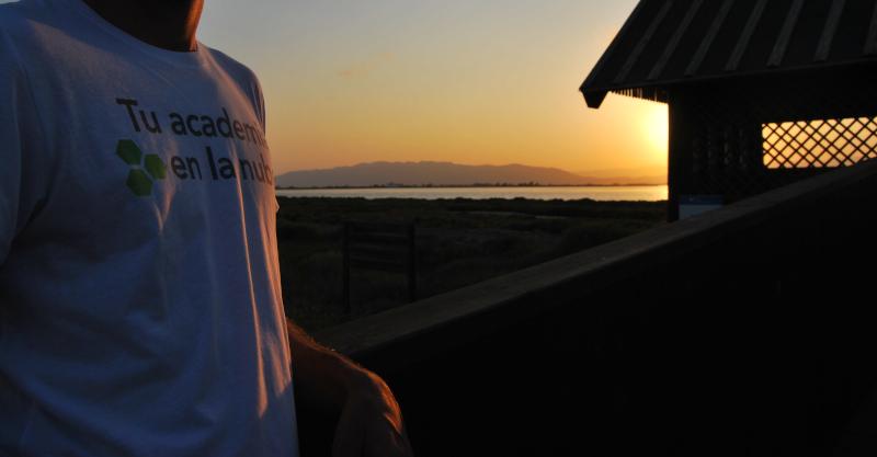 Persona con camiseta de Tu academia en la nube en un atardecer.
