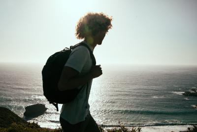 Estudiante con mochila paseando por la playa.