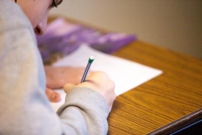 Estudiante tomando notas en papel.