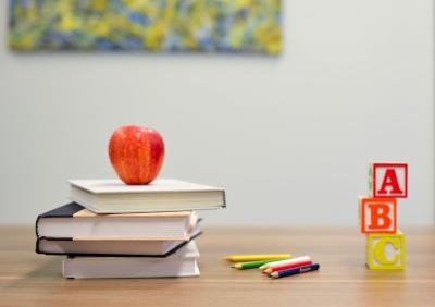 Manzana sobre pila de libros en un escritorio.