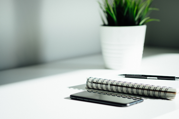 Mesa de estudio con un móvil, una libreta y un bolígrafo.