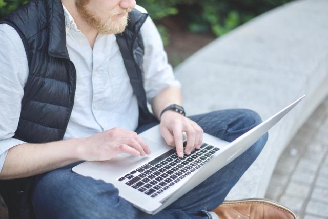 Hombre con un portátil sentado en un banco de piedra en la calle.