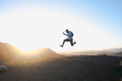 Hombre saltando sobre el suelo con el cielo y las montañas de fondo.