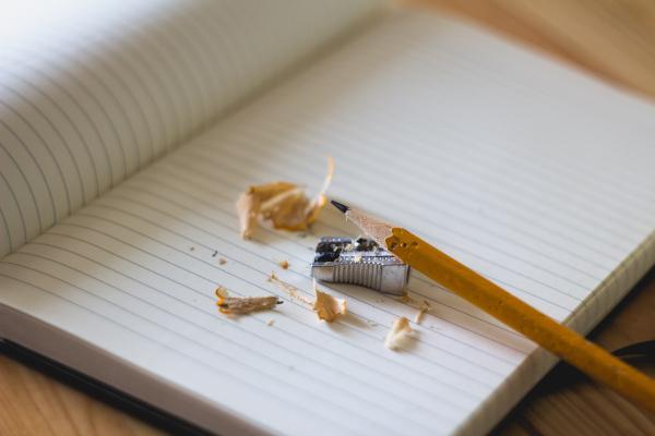 Lapicero, sacapuntas y restos de afilar el lapicero sobre un cuaderno.