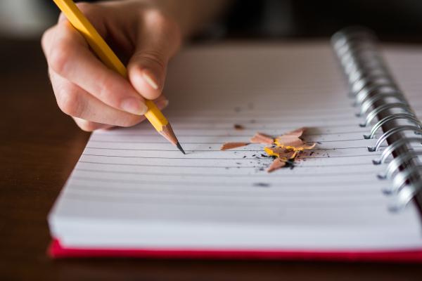 Mano escribiendo con un lápiz sobre un cuaderno de tapas rojas.