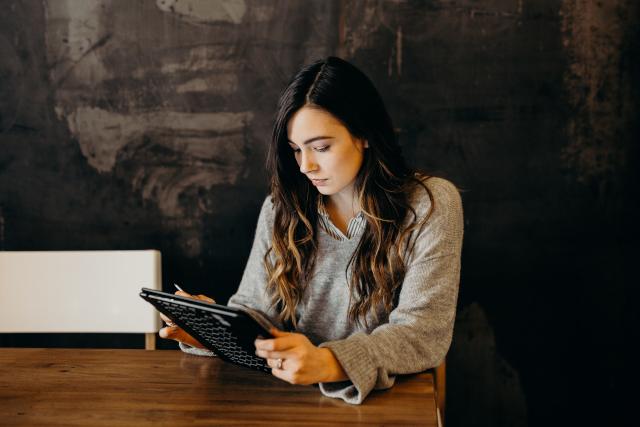 Mujer mirando una tablet mientras está sentada en un escritorio.