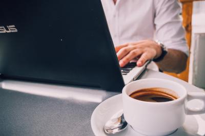 Persona trabajando con un portátil y tomando café.