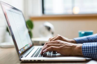 Profesor tomando notas en su ordenador portátil.
