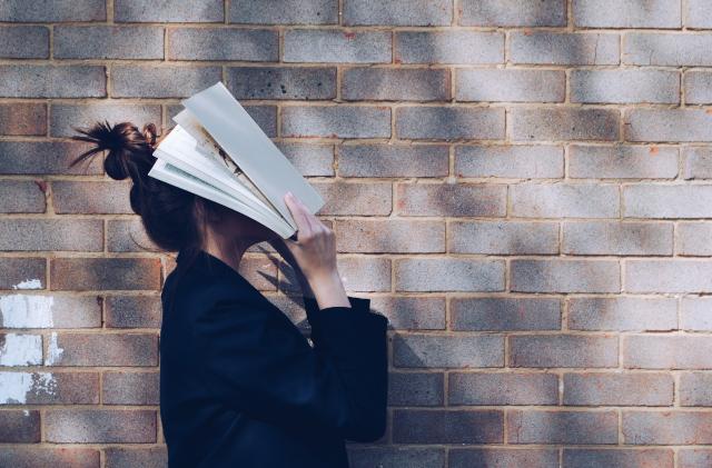 Chica de perfil con pared de ladrillo de fondo tapándose la cara con un libro abierto.