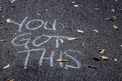 """Frase en inglés """"You got this"""" escrito con tiza sobre asfalto."""