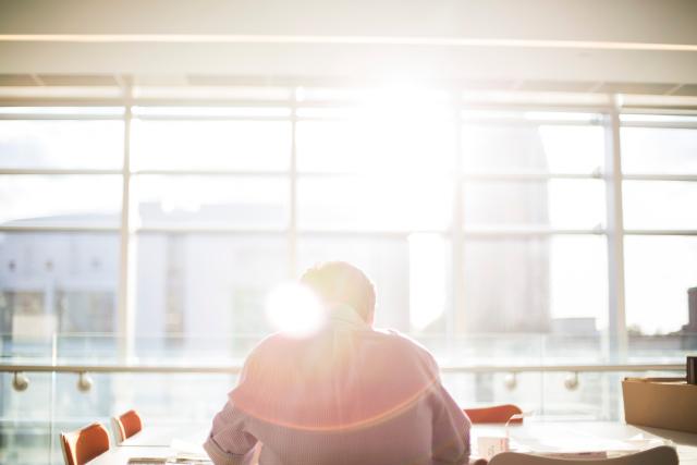 Hombre estudiando en una biblioteca con el sol de fondo entrando por la ventana.