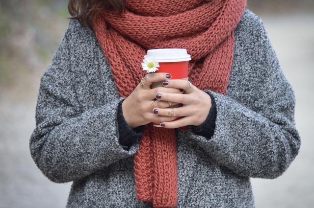 Chica por la calle con un vaso de café en las manos.