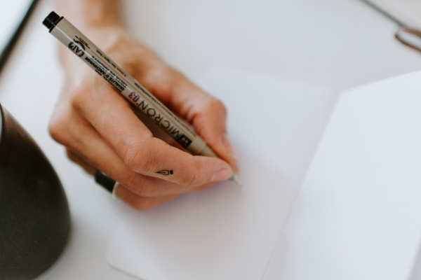 Mano tomando notas en un cuaderno con un bolígrafo.