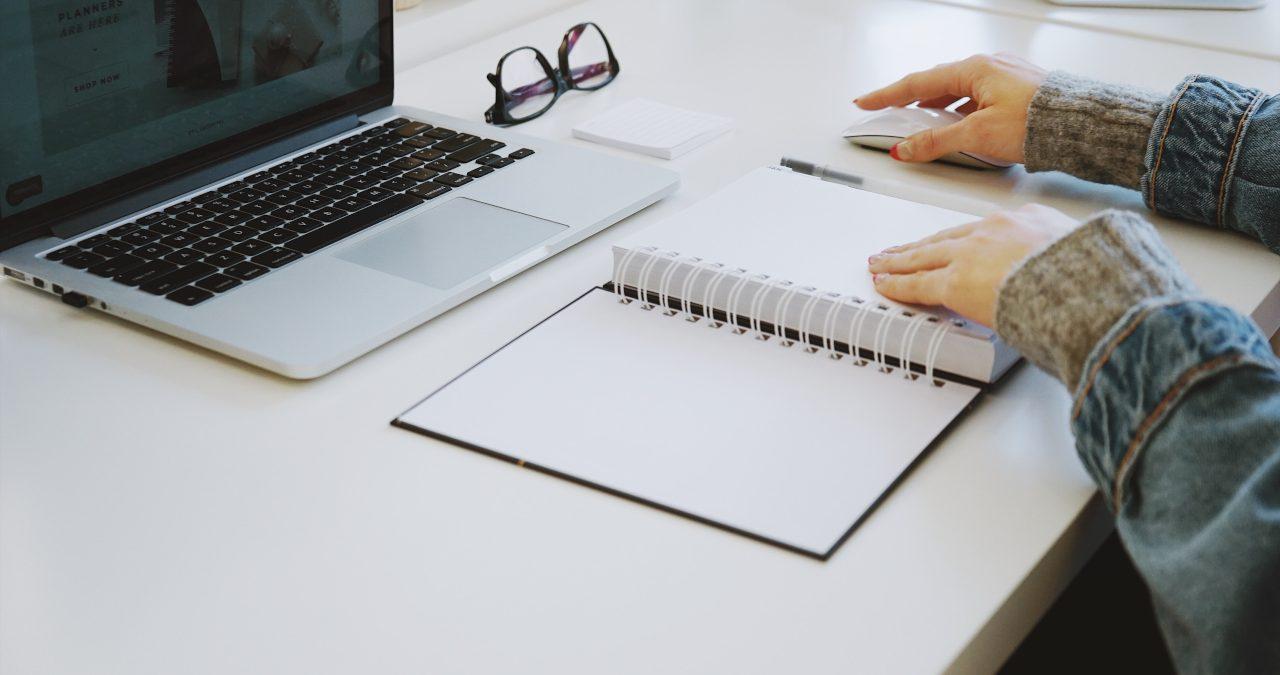 Manos de mujer, cuaderno y portátil sobre un escritorio de color blanco.