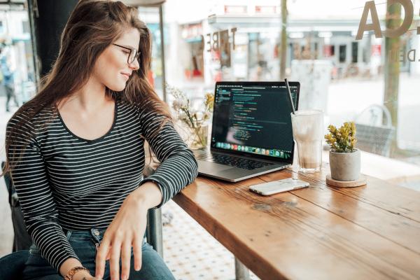Mujer estudiando con el portátil en la cafetería.