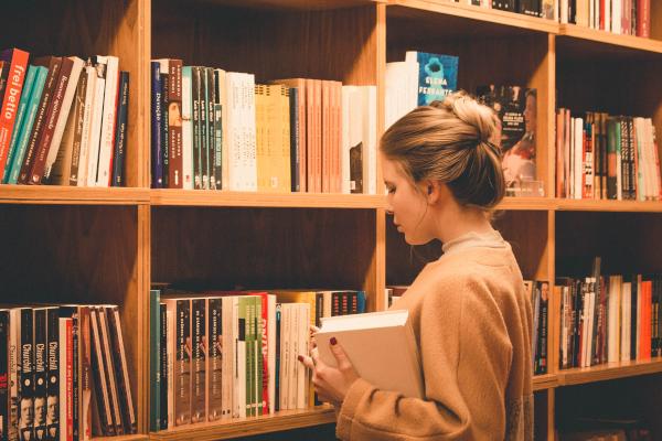 Mujer joven buscando libros de Física y Química en una biblioteca