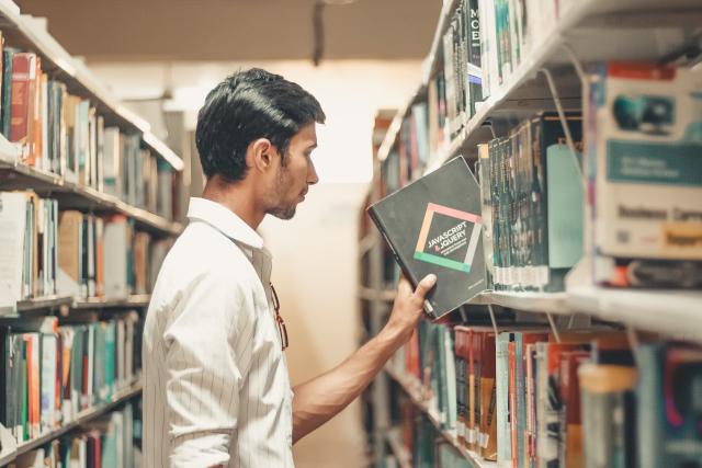 Hombre buscando libros de Física y Química en una biblioteca.